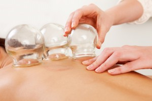 Detail of an acupuncture therapist removing a glass globe in a fire cupping procedure Fotolia_36496377